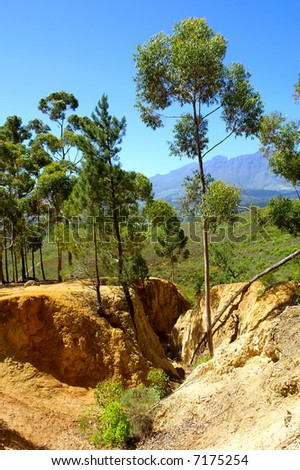 Yellow soil ravine - and scenic mountains as a background. Shot in Stellenbosch Mountain, Western Cape, South Africa. - stock photo