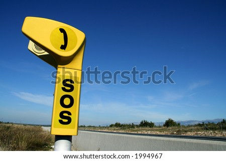 Yellow SOS  phone box at the highway - stock photo