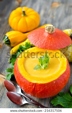 Yellow soup in a pumpkin on wooden table
