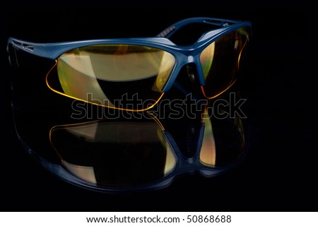 yellow sporting glasses on a black background - stock photo