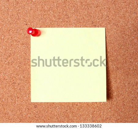 yellow sticker pinned on a cork bulletin board - stock photo