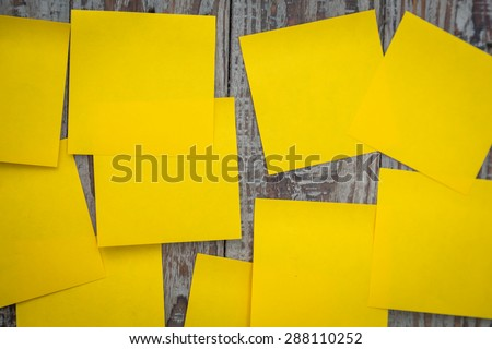 Yellow sticky note on wooden board - stock photo