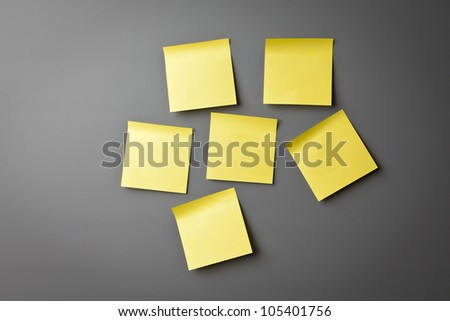Yellow sticky notes on a grey wall - stock photo