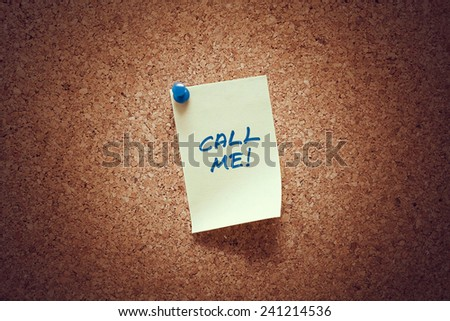 yellow sticky reminder note with call me message on corkboard. - stock photo