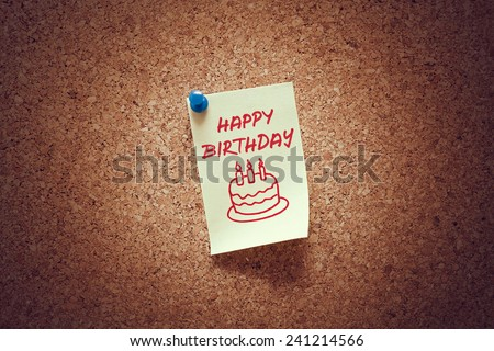 yellow sticky reminder note with happy birthday message and cake illustration on corkboard.  - stock photo