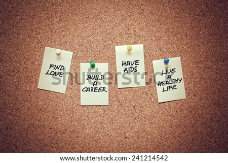 yellow sticky reminder notes with goals of life messages on corkboard. Future plans concept. - stock photo