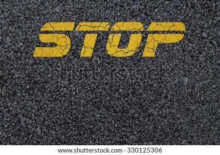 Yellow stop sign background on asphalt - stock photo