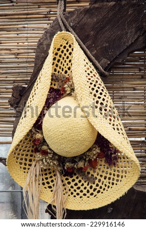 Yellow straw hat with decorative flower ribbon. - stock photo