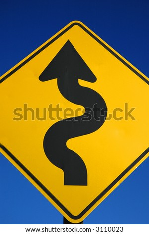 Yellow street sign for curves ahead with blue sky