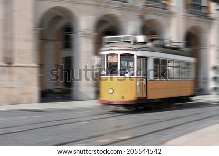 Yellow streetcar or tram in Lisbon showing speed with motion, in retro vintage look Portugal, Europe - stock photo
