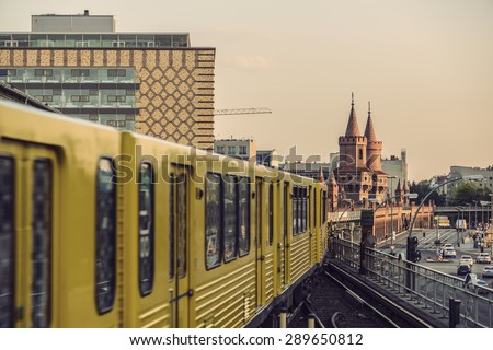 Yellow Subway train on trail to the historical bridge (Oberbaumbruecke) in Berlin, Germany,  Europe, Vintage filtered style - stock photo