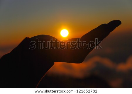 yellow sun in the palm of your hand - stock photo