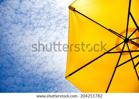 Yellow sun umbrella on a blue sky. Summer background. - stock photo