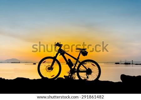 yellow sunrise at the beach and silhouette mountain bike - stock photo