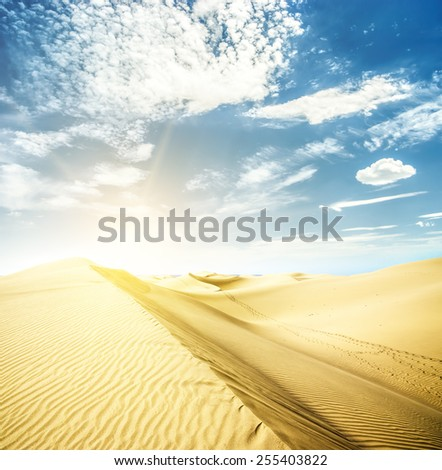 Yellow sunset in sand dunes with footprints. Canary islands, Maspalomas. - stock photo