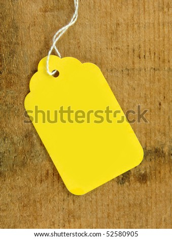 Yellow tag on wooden surface with copy space for your text. - stock photo