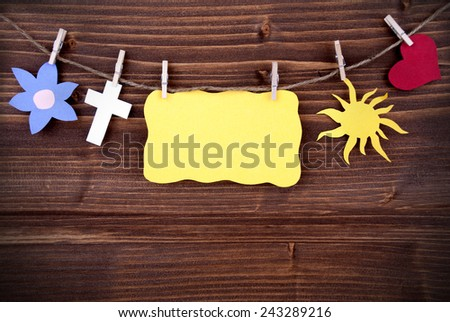 Yellow Tag Or Label With Heart And Flower And Cross And Sun On A Line With Copy Space Or Your Free Text Here On Wooden Background, Four Symbols, Vintage, Retro And Old Fashion Style With Frame - stock photo