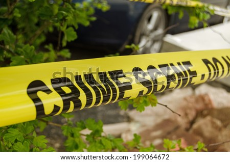 Yellow tape barrier surrounding a crime scene under investigation by the police. - stock photo