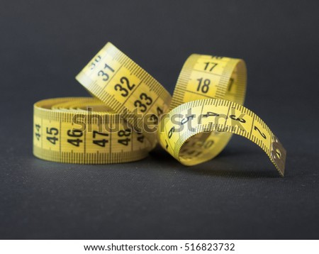 Yellow tape measure on rolled up on black background