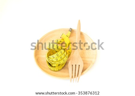 Yellow tape measure with fork in wooden plate on white background. Healthy lifestyle concept - stock photo