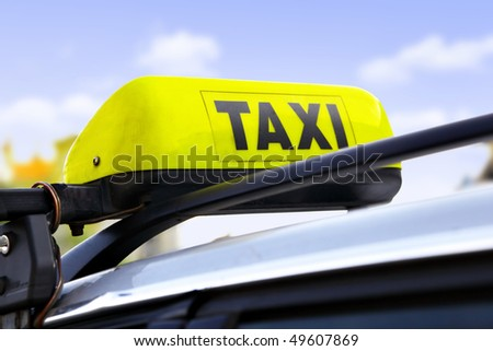 Yellow taxi sign on roof of car close-up