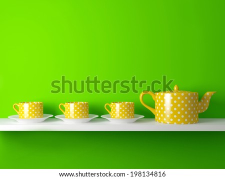 Yellow teapot and cups on the shelf in front of green wall.  - stock photo