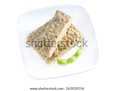 Yellow tempeh served on plate with edamame. - stock photo