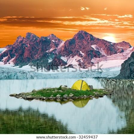 yellow tent in a mountain lake - stock photo