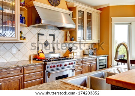 Yellow tones kitchen with tile decorated back-plash, kitchen appliances - stock photo