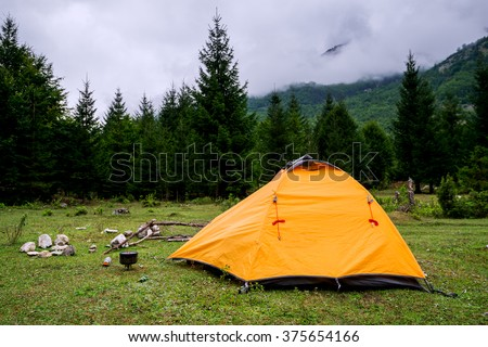 Yellow tourist tent on a glade in the mountains, camping and tourist camp for the night outdoors