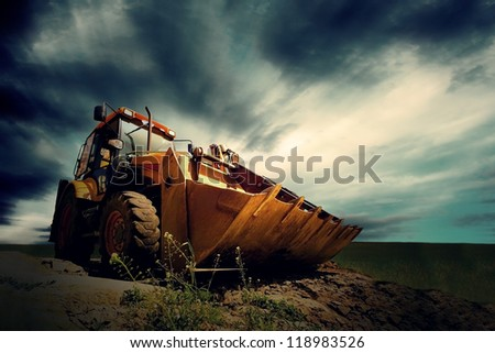 Yellow tractor on sky background - stock photo