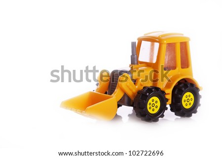 yellow tractor toy on a white - stock photo