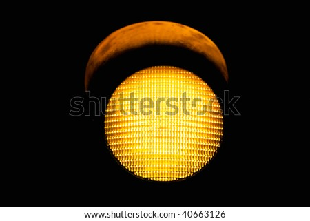 yellow traffic light, isolated on black background - stock photo