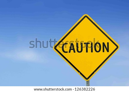 """Yellow traffic sign """"Caution""""  on the sky background - stock photo"""