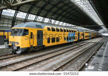 Yellow train in Amsterdam Central Station, Netherlands - stock photo