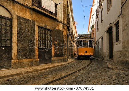 Yellow tram in Lisbon, Portugal. Small street in Alfama - stock photo