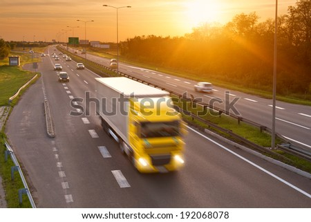 Yellow truck in the rush hour on the highway at dusk