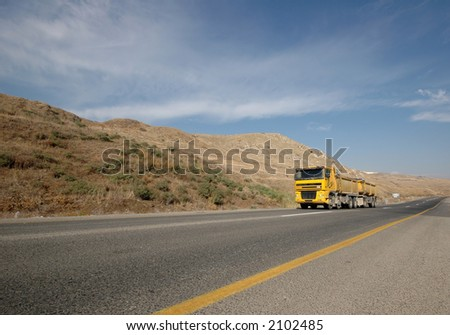 Yellow truck on an empty road - stock photo