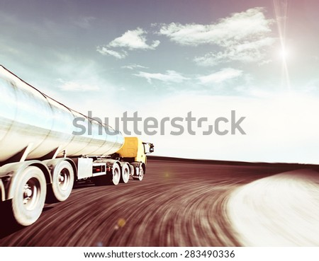 Yellow truck on blurry asphalt road over cloudy sky background - stock photo