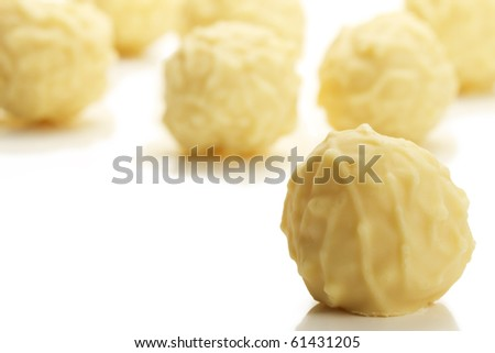 yellow truffle praline in front of many on white background