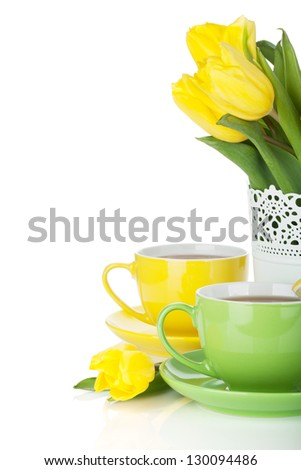 Yellow tulips and two tea cups. Isolated on white background