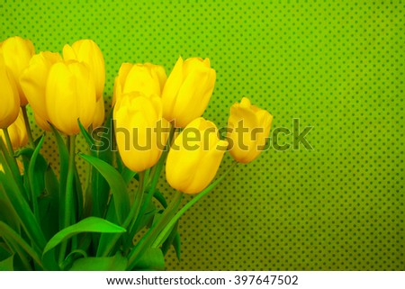 Yellow tulips on green background with space for message. Mother's Day background. Soft focus.