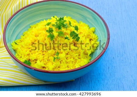 Yellow turmeric rice in a bowl garnish with chopped parsley. Blue background - stock photo