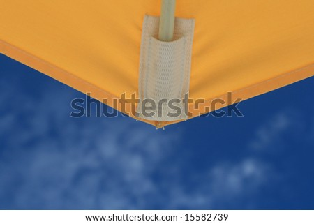 Yellow umbrella detail and blue sky background - stock photo