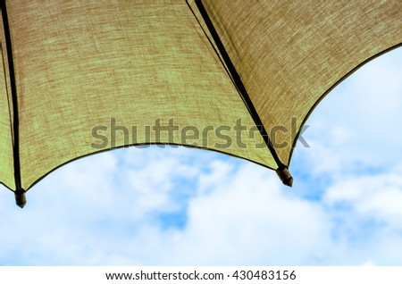 yellow umbrella in a clear blue sky, colorful sunshades umbrellas on blue sky - stock photo
