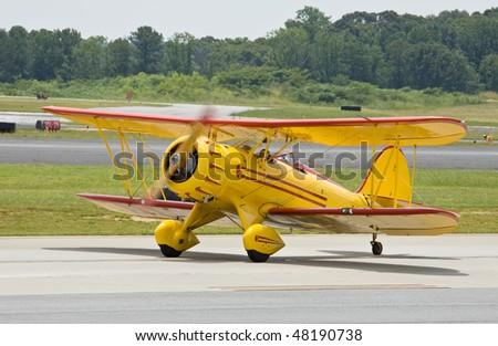 yellow vintage airplane landing - stock photo
