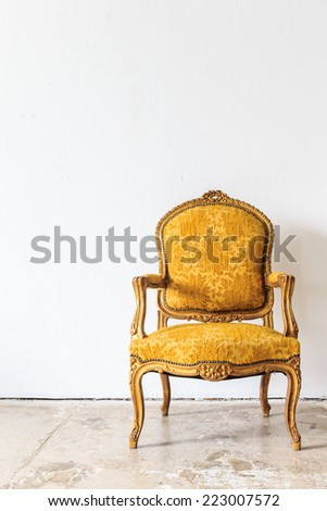 Yellow vintage armchair on white wall.