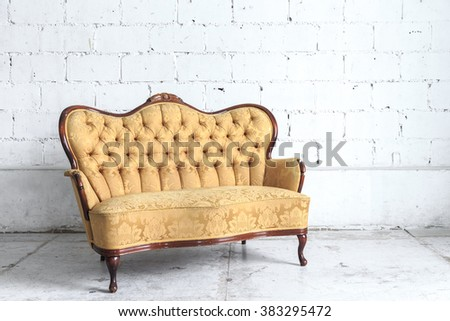 Yellow vintage sofa on white wall.