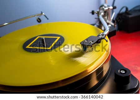 Yellow vinyl record played on a hi-end turntable record player close up standing on red wood stand - stock photo