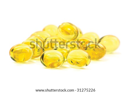 Yellow vitamin fish oil capsules, macro closeup of golden pills, isolated on white